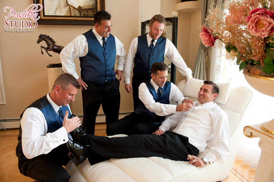 Groom's best man and friends helping him prepare for the big day